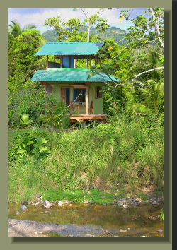 View from across the river Tigre of the small House in This Osa Peninsula Riverside Property